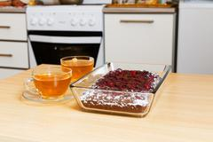 Two cup of tea and chokolate pie with cherry on the domestic kitchen - stock photo