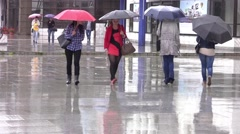 Young girls and other people with umbrellas circulating on a city street in Stock Footage