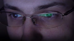 Close up shot of man in glasses surfing internet at night - stock footage