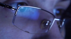 Close up shot of man in glasses surfing internet at night Stock Footage