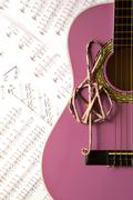 Violet guitar for children with treble clef on music sheets background Stock Photos