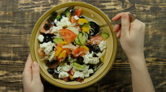 Female hand stirring fresh vegetable salad with cheese feta in the kitchen - stock footage