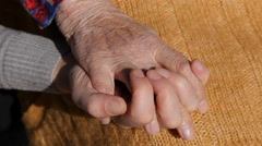 A young female hands comforting an elderly pair of hands of grandma close up. Stock Footage