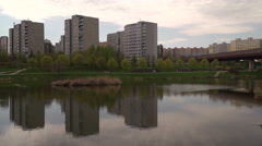 A small lake with the reflections of the buildings on pond Stock Footage