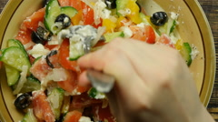 Stirring fresh vegetable salad with cheese feta in the kitchen - stock footage