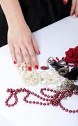 Woman hands a red and white bead Stock Photos