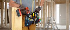Builder handyman with drill and wooden plank. Stock Photos