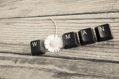 WOMAN wrote with keyboard keys on wooden background, black and white effect - stock photo