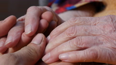A man's hands comforting an elderly pair of hands Stock Footage