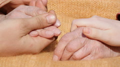 A young male and female hands comforting a old pair of hands outdoor. Stock Footage