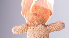 Teddy bear with head on fire slow motion Stock Footage