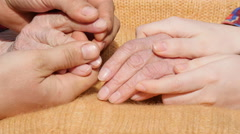 A young man's and woman's hands comforting a old pair of hands of grandmother Stock Footage
