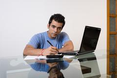A man sorting his finances on a laptop Stock Photos
