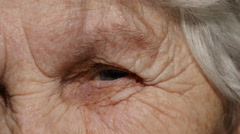 Close-up portrait of a old woman's gaze. Eye of grandmother - stock footage