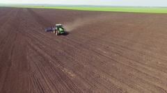 Aerial view of tractor cultivating field's soil in spring day - stock footage