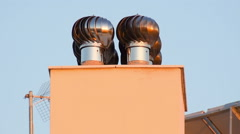 Chimney  ventilator fan system in motion on top of a house. - stock footage