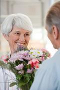 A senior man giving a senior woman flowers Stock Photos
