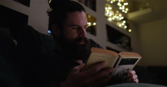 4k, An attractive young man relaxing and reading a novel at night. Stock Footage