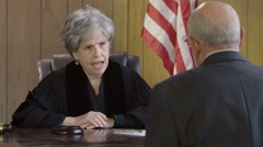 Older female judge nodding in agreement at her desk Stock Footage