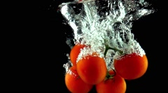 Bunch of red ripe tomatoes falls under water super slow motion video Stock Footage