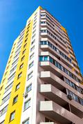 New tall apartment building against blue sky background - stock photo