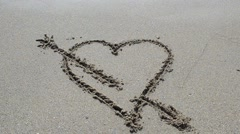 Wave washes over heart in the sand. Love and heart break concept. Stock Footage