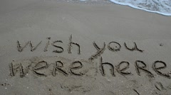 Conceptual wish you were here text handwritten in sand on a beach - stock footage