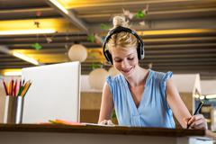 Graphic designer listening to headphones while using graphic tablet Stock Photos