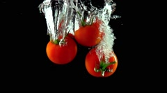 Three red ripe tomatoes fall under water super slow motion shot - stock footage