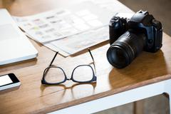 Mobile phone, spectacle and camera on desk Stock Photos