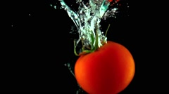 One red ripe tomato with green leaves falls under water super slow motion shot - stock footage