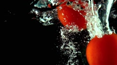 Several red tomatoes with green leaves fall under water super slow motion - stock footage