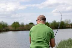 Fisherman in action, Fisherman holding rod in action Young man fishing on a lake - stock photo
