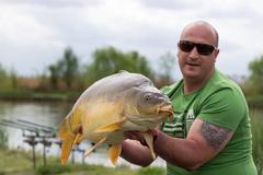 Carp and Fisherman, Carp fishing trophy Selective focus Stock Photos