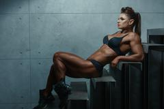 Female bodybuilder lying on the steps. Stock Photos