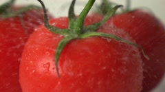 Small water drops hit red ripe tomato with green leaves super slow motion shot - stock footage