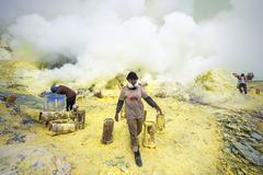 Sulfur Miners at Kawah Ijen Volcano in East Java, Indonesia - stock photo