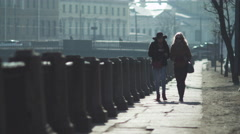 Two women are walking on the enbankment of river in european city Stock Footage
