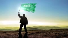 Successful silhouette man winner waving Saudi Arabia flag on top of the mount - stock footage