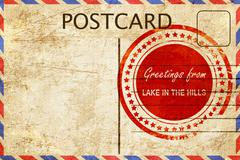 lake in the hills stamp on a vintage, old postcard - stock illustration