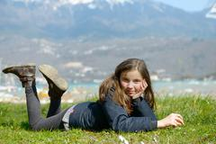 Pretty preteen is lying in the green grass Stock Photos
