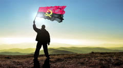 Successful silhouette man winner waving Angola flag on top of the mountain pe Stock Footage
