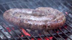 Turning traditional braai barbecue boerewors sausage on fire - stock footage
