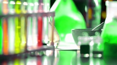 Flasks with green reagent, test tubes and beakers with multicolored reagents - stock footage