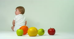 Happy baby playing with apple, orange,  grapefruit Stock Footage