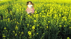 Stock Video Footage of Beauty young girl running on yellow rape field in rural countryside.