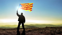 Successful silhouette man winner waving Catalonia flag on top of the mountain Stock Footage
