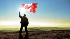 Successful silhouette man winner waving Canada flag on top of the mountain pe Stock Footage