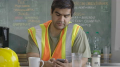 Construction worker looking at phone Stock Footage