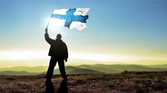 Successful silhouette man winner waving Finland flag on top of the mountain p Stock Footage